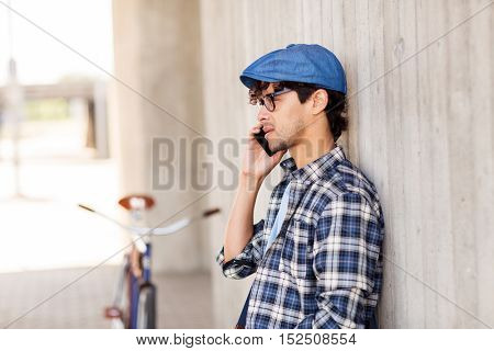 people, communication, technology and lifestyle - hipster man calling on smartphone and fixed gear bike on city street