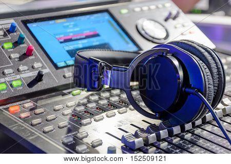 Studio headphones lying on the audio mixer. Live and studio equipment.