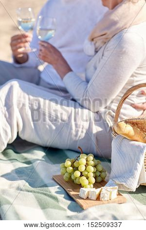 family, age, holidays, leisure and people concept - close up of happy senior couple with picnic basket sitting on blanket on summer beach