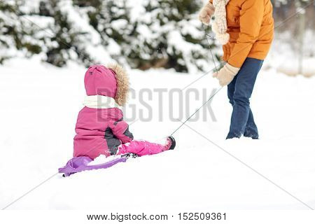 family, sledding, season and people concept - father pulling sled with child outdoors in winter