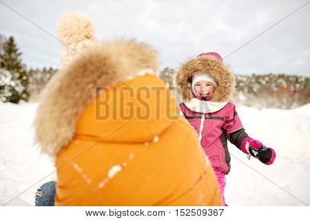 family, parenthood, fatherhood, season and people concept - happy father and little girl in winter clothes playing outdoors