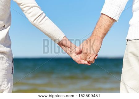 family, age, travel, tourism and people concept - close up of senior couple holding hands on summer beach