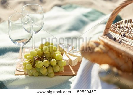 food, holidays, celebration and summer concept - close up of picnic basket with grapes, wine glasses and cheese on beach