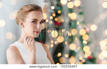 jewelry, luxury, holidays and people concept - smiling woman in white dress with diamond earring and ring over christmas tree lights background