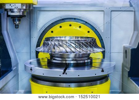 Metalworking. High-precision CNC machine processes steel turbine wheel.