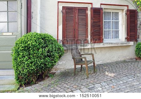 The yard of an apartment house with shutters on the windows wooden chair and bushes.