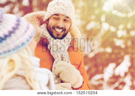 holidays, christmas, season and people concept - happy friends or couple in winter forest