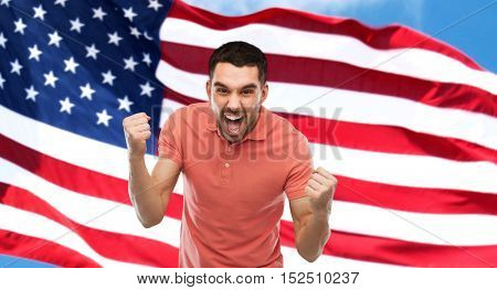 emotion, aggression, patriotism, gesture and people concept - angry young man showing fists over american flag