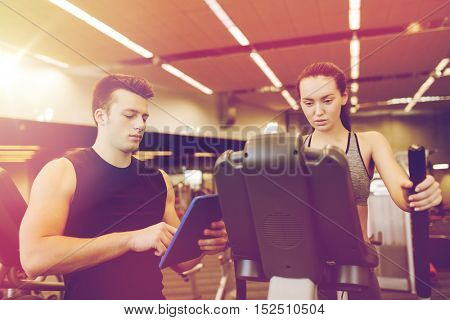 sport, fitness, lifestyle, technology and people concept - woman and trainer with tablet pc computer exercising on stepper in gym