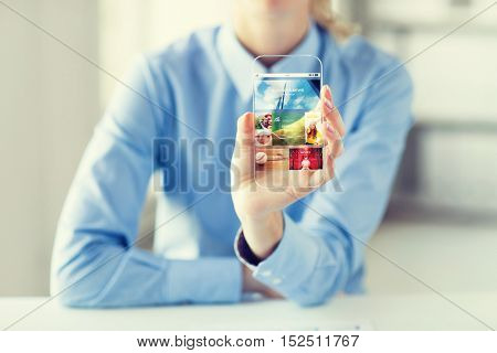 business, technology, mass media and people concept - close up of woman hand holding and showing showing news application on transparent smartphone screen at office