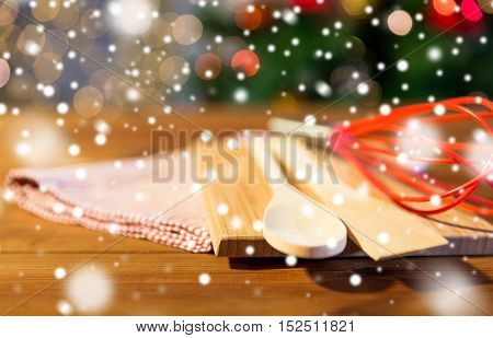baking, cooking, christmas and food concept - close up of kitchenware set and towel on wooden cutting board at home kitchen