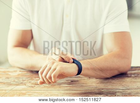 business, technology and people concept - close up of male hands with heart-rate watch at home