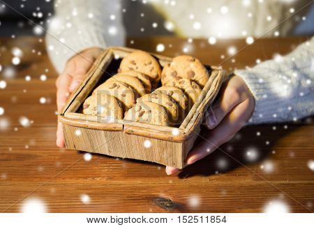 baking, cooking, people and food concept - close up of woman with oat cookies sitting at wooden table at home