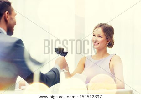 restaurant, couple and holiday concept - smiling young woman with glass of red wine looking at boyfriend or husband at restaurant