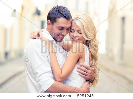 summer holidays, love, travel, tourism, relationship and dating concept - romantic happy couple hugging in the street