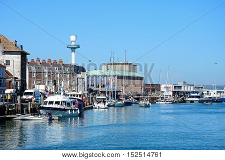 WEYMOUTH, UNITED KINGDOM - JULY 18, 2016 - Yachts and boats in the harbour with quayside buildings and the pavilion to the rear Weymouth Dorset England UK Western Europe, July 18, 2016.