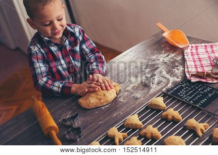 Child prepares homemade biscuits in the kitchen