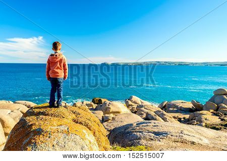 Boy standing at the edge of the rock and looking into the sea at Port Elliot South Australia
