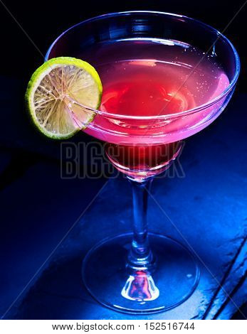 Berry alcohol cocktail with slice lemon on black background. Alcohol cocktail in martini glass.