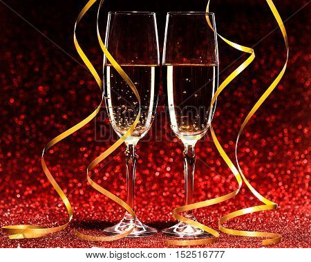 glasses of champagne with yellow holidays ribbons, on red background