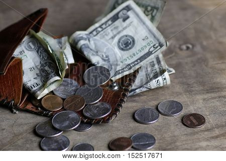 money on a wooden table bills and coins pocket change