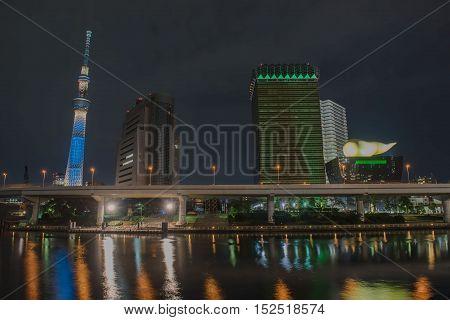 TOKYO  , JAPAN - OCTOBER 11 ,2016 : view of Sumida River with Tokyo Skytree and The Asahi Beer at Night , Tokyo, Japan. October 11 2016.