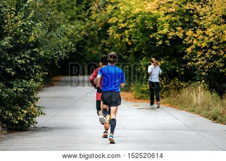two young men athletes runners run a marathon in autumn city Park