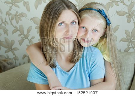 Embracing mother and her blonde teenage daughter family portrait
