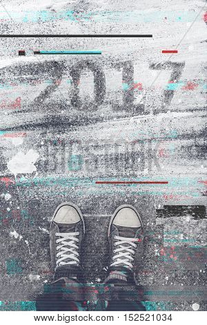 Happy New 2017 Year concept with digital glitch effect top view of young man sneakers standing at the street