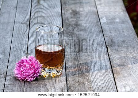 Glass of whiskey with flower on the old table in autumn garden's