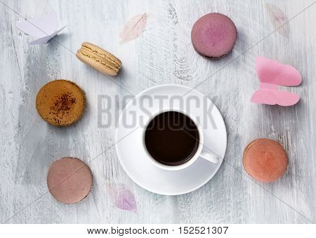 A photo of a cup of coffee with various pastel coloured macarons and paper butterflies