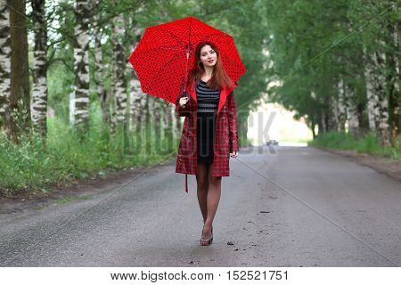 beautiful girl in a red raincoat with an umbrella walks in the rain