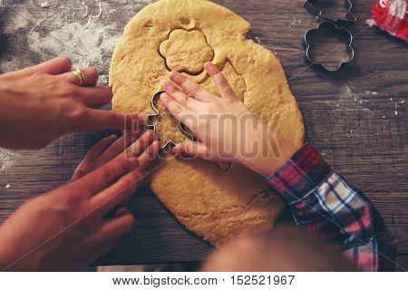 Top view of cutting gingerbread of metal molds by children's hands