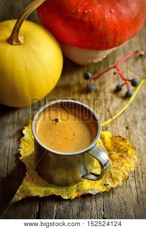 Autumn cup of coffee and pumpkin on wooden background