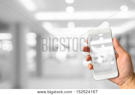 hand holding smart phone taking picture of blurred bokeh lights background in building