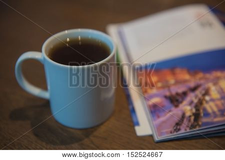 White tea cup on a wooden table and Travel Magazine.