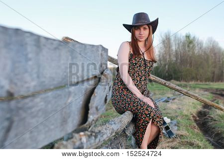 young sweet girl in a cowboy hat and red coat on a warm day in spring nature