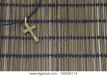 Gold cross on the brown wicker mat