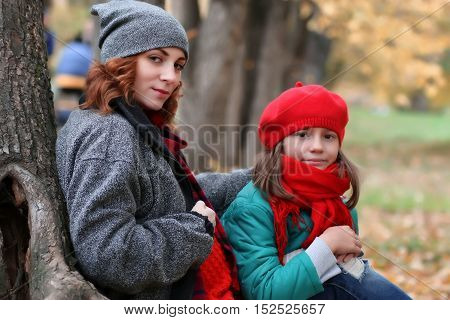 beautiful European family mother and daughter on a walk in a beautiful autumn park