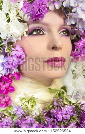 The beautiful girl in a makeup of pink shades and flowers phloxes around the head.