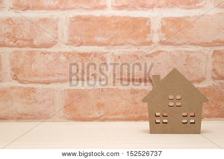 Miniature house and trees in front of brick wall. New house concept.