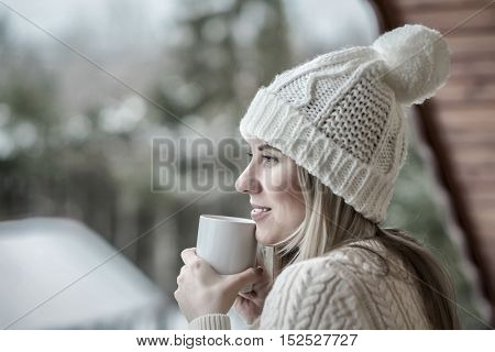 Female in white with cup of coffee at the winter weather