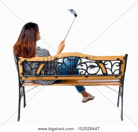 Back view of woman to make selfie stick portrait sitting on the bench. girl watching.  backside view person. Isolated over white background. Brunette sitting on bench photographed using selfie stick