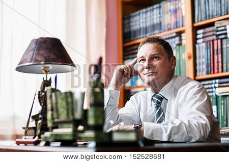Confident businessman sitting at the tabble in his home office