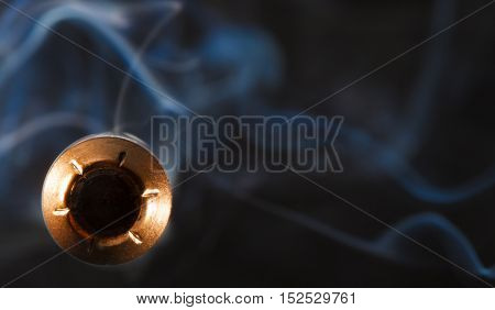 Hollow point with a copper coating and smoke coming at the camera