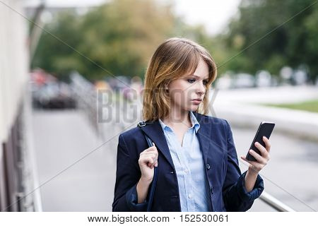 Businesswoman looking seriously on smartphone and walking outdoors
