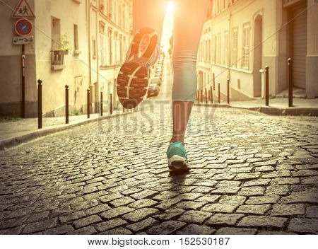Running woman. Close-up view foots of runner jogging at sunny day. Female fitness model training outside in Paris City.