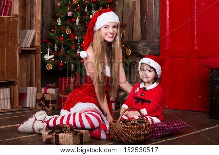 Cute girls sitting with presents near Christmas tree, smiling and having fun. Xmas atmosphere at home. New year eve.