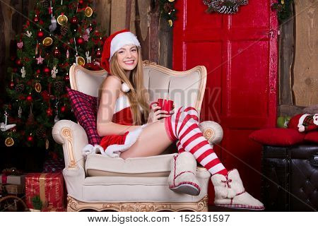 Beautiful and sexy Santa female having fun and smiling near the Christmas tree, sitting in vintage chair. New year atmosphere. Xmas girl.