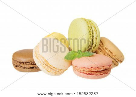Several multicolored macaroons pastel colors with green mint leaves isolated on white background
